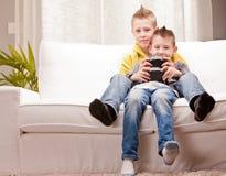 Pequeños hermanos que juegan videojuegos juntos Foto de archivo libre de regalías