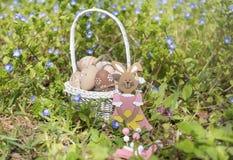 Pequeños huevos de Pascua beige en una cesta y un conejo blancos Foto de archivo