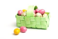 Pequeños huevos de Pascua coloridos en una cesta de mimbre verde Imágenes de archivo libres de regalías