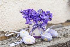 Pequeños huevos de Pascua en una cesta blanca con las violetas Imagenes de archivo