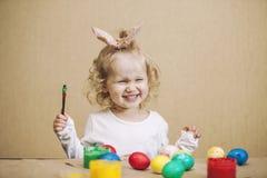 Pequeños huevos de Pascua lindos del color del bebé en la tabla en los colores, felices Fotografía de archivo libre de regalías