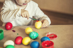 Pequeños huevos de Pascua lindos del color del bebé en la tabla en los colores, felices Fotografía de archivo