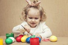 Pequeños huevos de Pascua lindos del color del bebé en la tabla en los colores, felices Fotos de archivo libres de regalías
