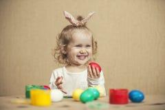 Pequeños huevos de Pascua lindos del color del bebé en la tabla en los colores, felices Imágenes de archivo libres de regalías