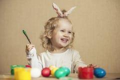 Pequeños huevos de Pascua lindos del color del bebé en la tabla en los colores, felices Foto de archivo