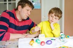 Pequeños huevos preescolares rubios del colorante del muchacho y del padre del niño para el día de fiesta de Pascua Foto de archivo libre de regalías