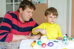 Pequeños huevos preescolares rubios del colorante del muchacho y del padre del niño para el día de fiesta de Pascua Imagen de archivo