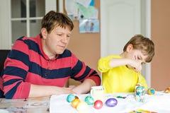 Pequeños huevos preescolares rubios del colorante del muchacho y del padre del niño para el día de fiesta de Pascua Fotos de archivo