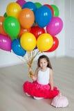 Pequeños juegos de la muchacha con los globos coloridos Fotografía de archivo libre de regalías