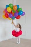 Pequeños juegos de la muchacha con los globos coloridos Imagen de archivo