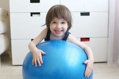 Pequeños juegos de niños con un fitball azul grande Fotos de archivo