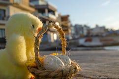 Pequeños juguete y cesta lindos del pollo con dos huevos de Pascua en el mar doc. - concepto de pascua fotos de archivo libres de regalías