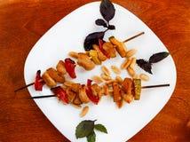Pequeños kebabs del pollo con el papel y el calabacín Fotografía de archivo