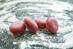 pequeños macarrones púrpuras deliciosos en la harina de trigo blanca desmenuzable en fondo negro fotografía de archivo