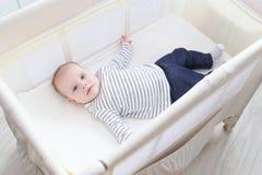Pequeños 3 meses preciosos de bebé que miente en pesebre del viaje Foto de archivo