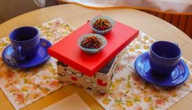 Pequeños molletes hermosos en una caja roja con las tazas de té en ambos lados Imagen de archivo libre de regalías