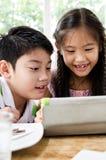 Pequeños muchacha y muchacho asiáticos con la tableta Fotografía de archivo
