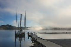 Pequeños muelle y gabarra por el lago imagen de archivo libre de regalías