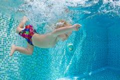 Pequeños natación y salto del bebé en piscina con la diversión Fotografía de archivo