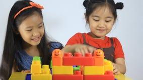 Pequeños niños asiáticos que juegan con los bloques almacen de metraje de vídeo