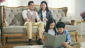Pequeños niños asiáticos que se sientan en el libro de lectura de la alfombra almacen de video