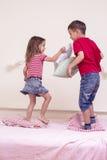 Pequeños niños caucásicos que tienen una batalla divertida de la almohada en cama dentro Imagen de archivo