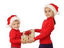 Pequeños niños con el rectángulo de regalo amarillo de la Navidad Foto de archivo