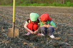 Pequeños niños con la pala en campo Imagen de archivo libre de regalías