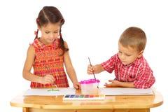 Pequeños niños con las pinturas de la acuarela Fotos de archivo