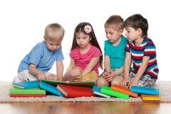Pequeños niños con los libros en el piso Imagen de archivo libre de regalías