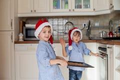 Pequeños niños dulces, hermanos del muchacho, preparando al cocinero del pan del jengibre Imagen de archivo libre de regalías