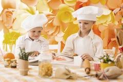 Pequeños niños felices bajo la forma de cocinero para cocinar el desayuno delicioso Foto de archivo libre de regalías