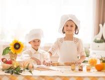 Pequeños niños felices bajo la forma de cocinero para cocinar la comida deliciosa Foto de archivo libre de regalías
