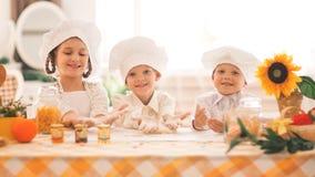 Pequeños niños felices bajo la forma de cocinero para cocinar un desayuno delicioso en la cocina Foto de archivo libre de regalías