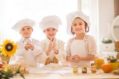 Pequeños niños felices bajo la forma de cocinero para preparar comidas deliciosas Fotografía de archivo libre de regalías
