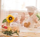 Pequeños niños felices bajo la forma de cocinero para preparar delicioso Fotografía de archivo