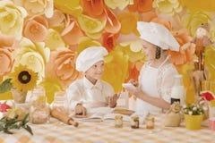 Pequeños niños felices bajo la forma de cocinero para preparar delicioso Imagen de archivo