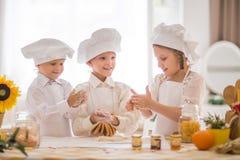 Pequeños niños felices bajo la forma de cocinero para preparar delicioso Foto de archivo