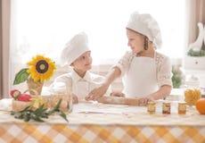 Pequeños niños felices bajo la forma de cocinero para preparar delicioso Foto de archivo libre de regalías