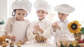 Pequeños niños felices en la forma de un cocinero para preparar platos deliciosos Foto de archivo