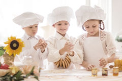 Pequeños niños felices en la forma de un cocinero para preparar platos deliciosos Fotografía de archivo
