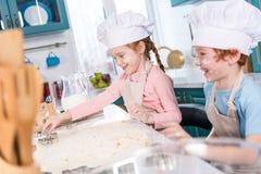 pequeños niños felices en los sombreros del cocinero que preparan las galletas juntas Fotos de archivo libres de regalías