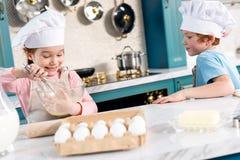 pequeños niños felices en sombreros del cocinero y delantales que hacen la pasta Fotografía de archivo libre de regalías