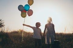 Pequeños niños felices que juegan en el camino en el tiempo de la puesta del sol Fotos de archivo