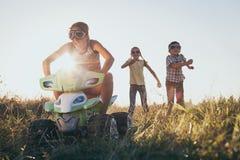Pequeños niños felices que juegan en el camino en el tiempo de la puesta del sol Imagenes de archivo