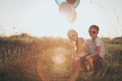 Pequeños niños felices que juegan en el camino en el tiempo de la puesta del sol Fotos de archivo libres de regalías