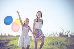 Pequeños niños felices que juegan en el campo en el tiempo del día Fotos de archivo
