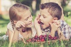 Pequeños niños felices que mienten cerca del árbol con una cesta de cherr Fotografía de archivo libre de regalías