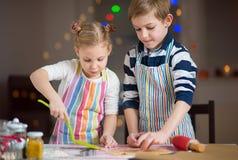 Pequeños niños felices que preparan las galletas de la Navidad Imagen de archivo libre de regalías
