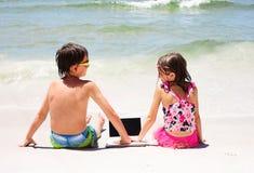Pequeños niños felices que se sientan en la playa con el ordenador portátil Fotos de archivo